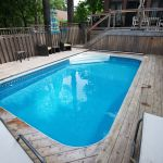 In-ground swimming pool surrounded by beautiful decking