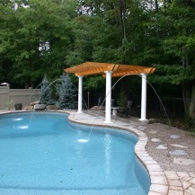 petite fountain streams into a large in-ground pool - located in Ottawa