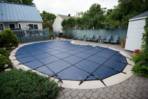 A bean shaped pool with a safety cover
