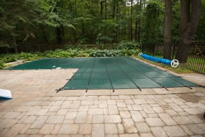 An in-ground pool with a safety cover