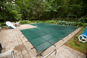 An in-ground pool with a safety cover installed
