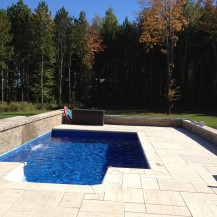 Cozy in-ground swimming pool with waterfall