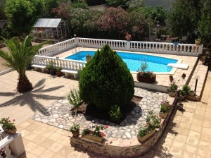 Beautiful backyard landscape with a semi-inground pool.