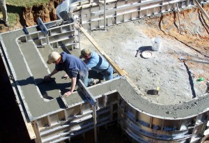 Two workers laying out inground pool steps using concrete forms.