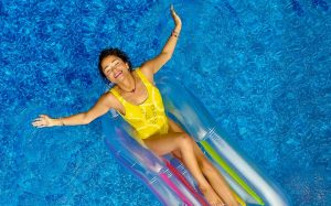 A smiling woman in a yellow bathing suit floats on an inflatable pool chair, enjoying herself thanks to smart swimming pool equipment.