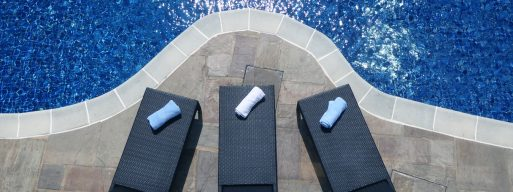 Three poolside deck chairs sit on a stone patio by the side of a clear, beautiful azure pool.