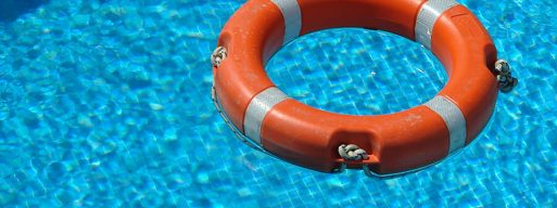 An orange life saver floats in a crystal-clear pool, part of the swimming pool's safety equipment.