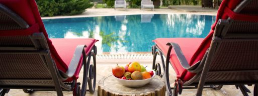 View of a backyard pool between two pool chairs and a side table filled with refreshments