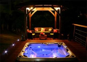 Beautiful scenic hot tub installation at night with patio floor lights