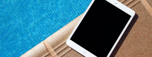 iPad sitting on the edge of a dock next to an inground swimming pool
