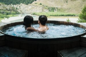 Two people soaking in a hot tub looking at the beautiful valley view