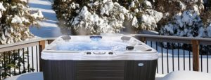 steaming hot tub with snow and trees in the backdrop