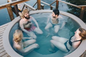 four people sit in a hot tub outdoors