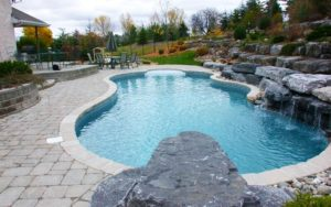 A pool with many large rocks covering one side of it