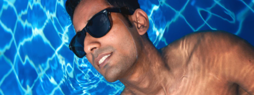 tanned man floats in his new pool wearing sunglasses