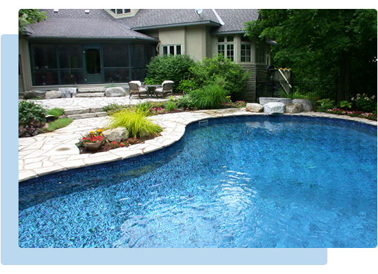 A landscaped backyard with an in ground pool