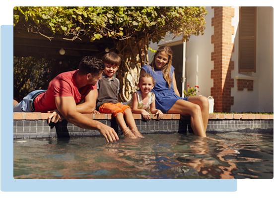 A family sitting with their legs in the pool