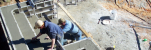 workers from Poolarama build stairs for an inground swimming pool