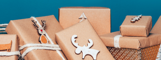 presents wrapped in brown paper piled infront of blue backdrop