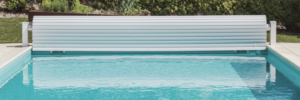 pool cover rolled up at the end of an inground swimming pool